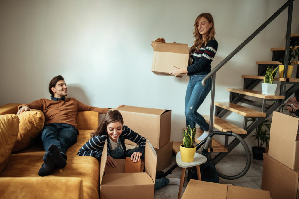 Group of friends packing their stuff for moving in new apartment